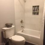 New bathroom in basement renovation, black slate flooring and modern white porcelain tile