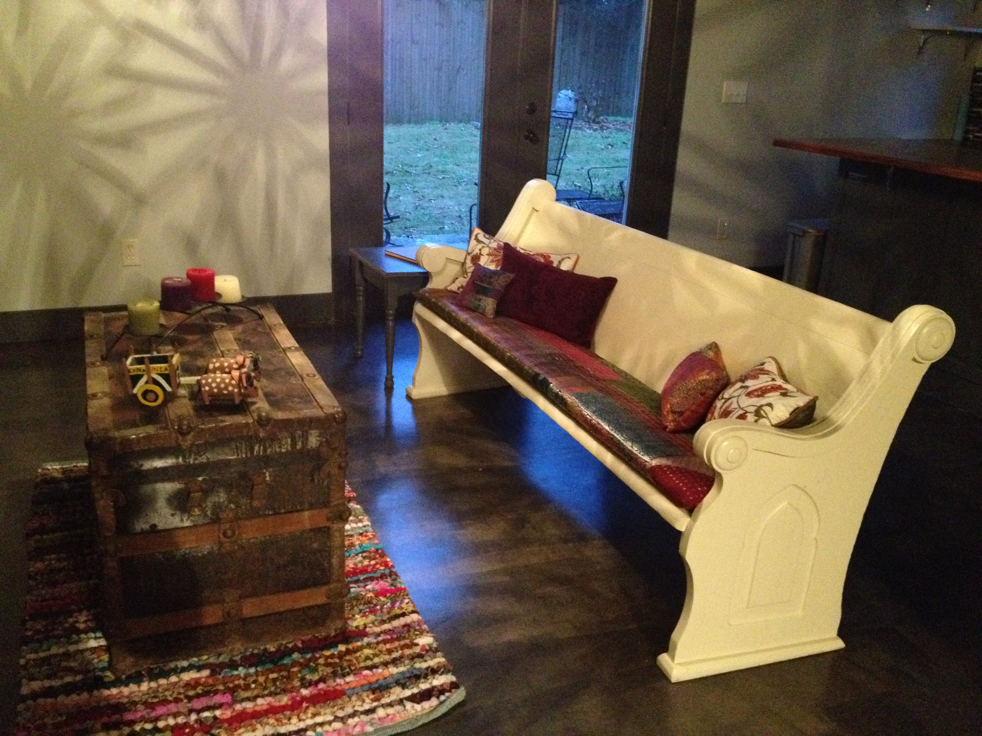 Newly renovated Hoover basement with antique church pew and concrete floors