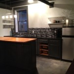 Basement kitchen with refurbished cabinets and countertops made from old wooden doors